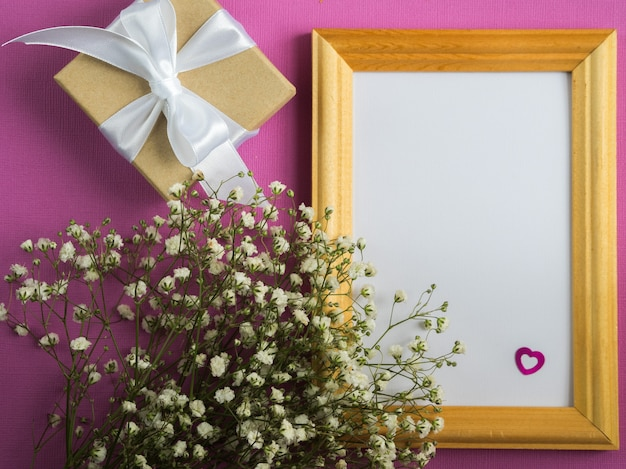 Empty frame mock up. white flowers. wrapped gift box.