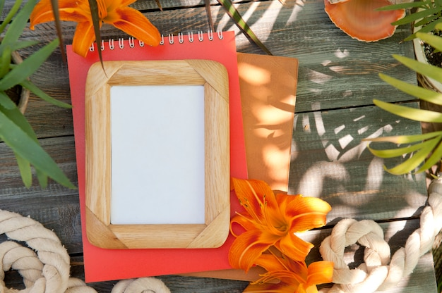 Empty frame mock up with lily flowers, outdoor photo
