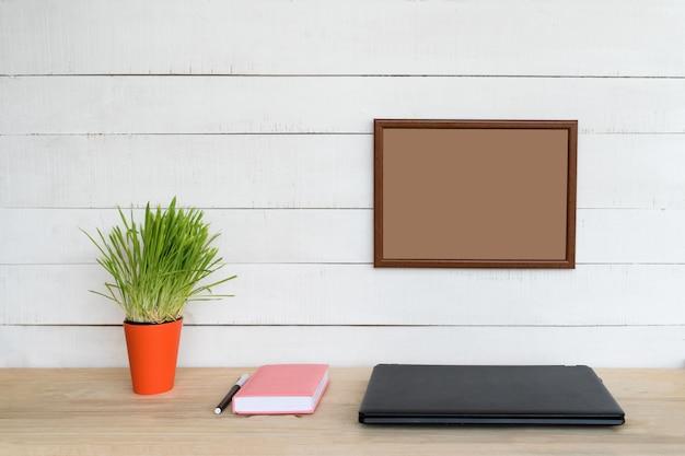 Пустая рамка на белой стене. закрытый ноутбук, блокнот и ручка. зеленое комнатное растение. домашнее рабочее место. место для текста