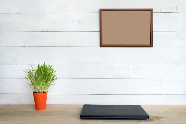 흰 벽에 빈 프레임입니다. 닫힌 노트북과 녹색 관엽 식물. 가정 직장. 텍스트 배치