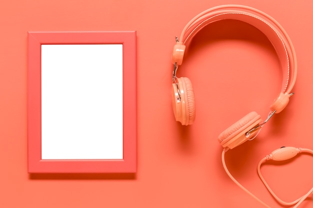 Empty frame and pink earphones on colored surface
