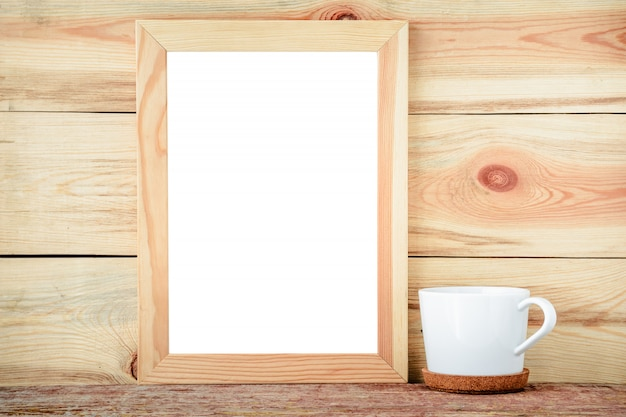Empty frame and white cup on a wooden background.