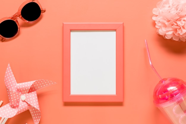 Empty frame with feminine stuff placed on red background