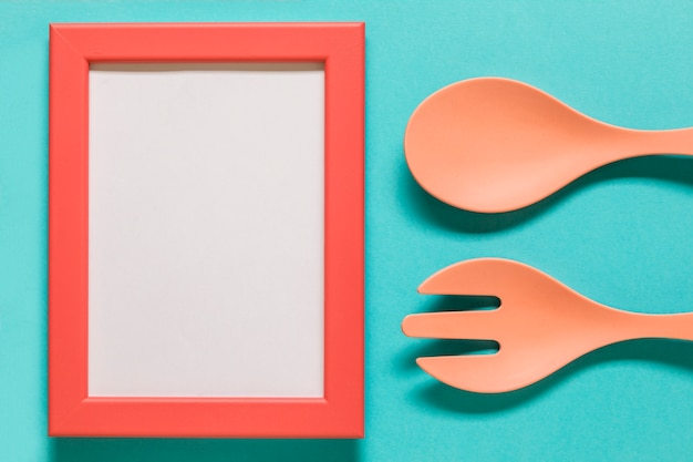 Empty frame with spoon and fork on blue background