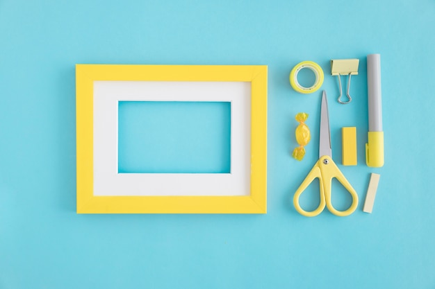 An empty frame with white and yellow border and stationeries on blue background