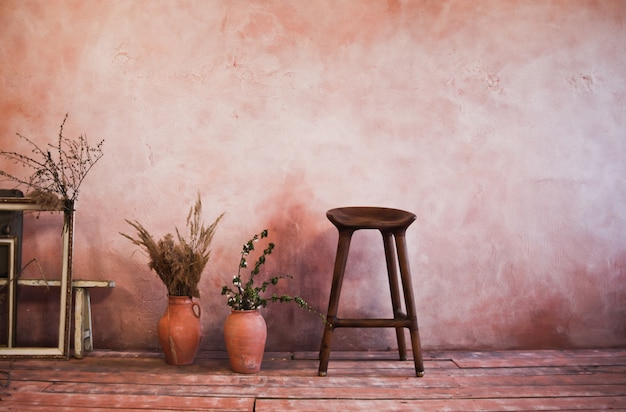Empty frames, wooden chair, clay jugs with branches on rustic vintage room