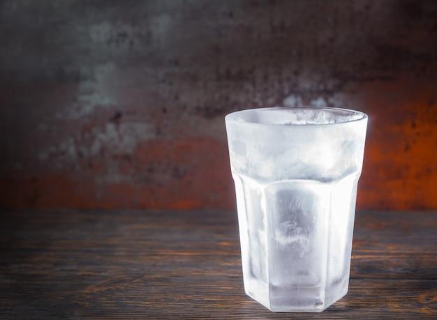 古い暗い机の上に空の冷凍ビアグラス。飲み物と飲み物のコンセプト