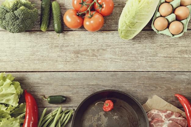 空のフライパンと野菜、トップビューの背景