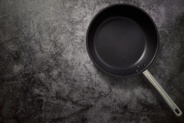 Empty frying pan black on dark stone work surface with copyspace