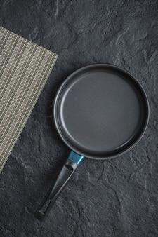 Padella vuota per cucinare posta su sfondo nero