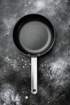 Empty frying pan set with copy space for text or food with copy space for text or food, top view flat lay, on black dark stone table background