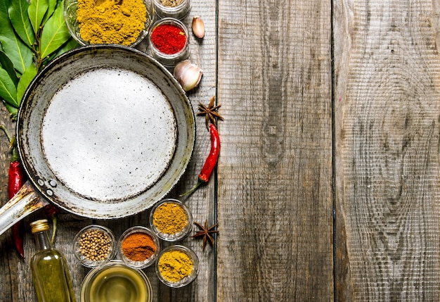 Empty frying pan with aromatic spices and herbs on wooden table. top view
