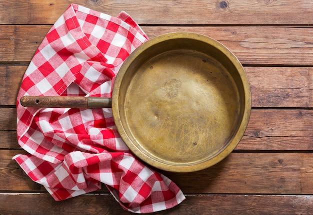 Пустая сковорода с красной скатертью на деревянном столе, вид сверху