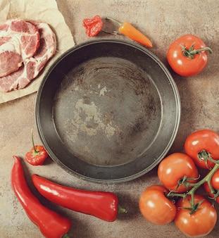 Пустая сковорода с овощами и сырым мясом вокруг, вид сверху