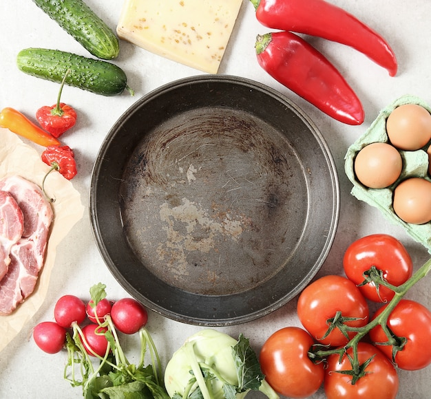 Empty frying pan with vegetables around, top view