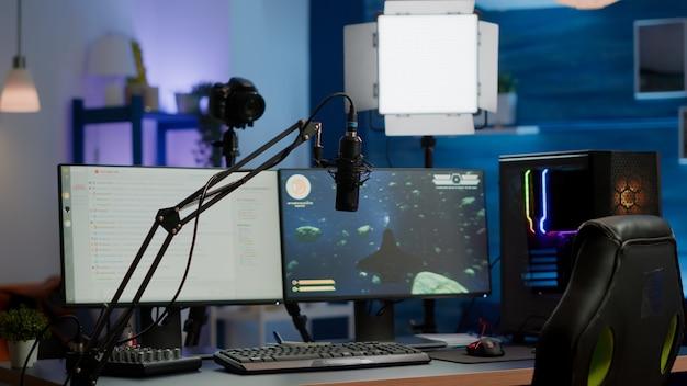 Rgb ledを備えた空のゲームスタジオは、オンライン競争をストリーミングするための強力なパーソナルコンピューターを点灯します。バーチャルトーナメント用に準備されたストリームチャット、誰もいないリビングルームで表示