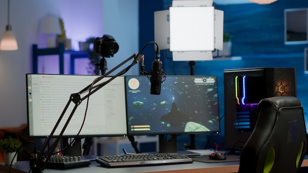 Empty gaming studio with rgb led lights powerful personal computer for streaming online competition. display with stream chat prepared for virtual tournament, living room with nobody in