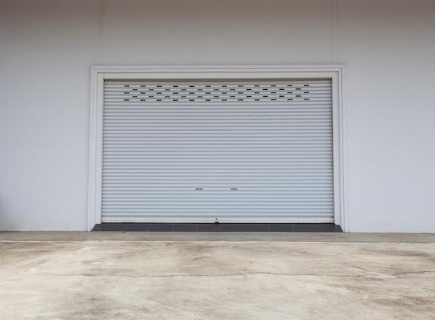 Empty garage with shutter door or roller door and concrete floor , industrial building