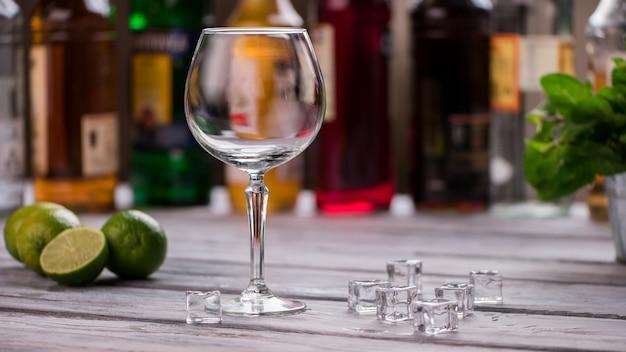 Пустой стакан и кубики льда. известь на деревянной поверхности. ингредиенты для прохладительного напитка. как насчет коктейля.