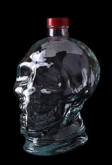 Empty glass bottle in the form of a skull on a black background.