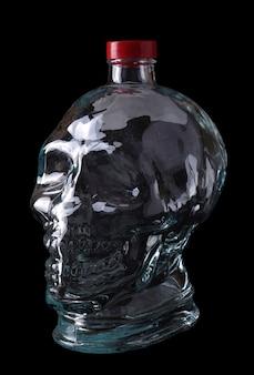 Пустая стеклянная бутылка в виде черепа на черном фоне.
