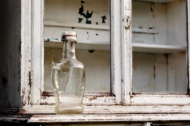 Empty glass bottle on an old white kitchen cabinet
