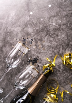 Empty glass and champagne bottle with party decorative item on concrete textured background