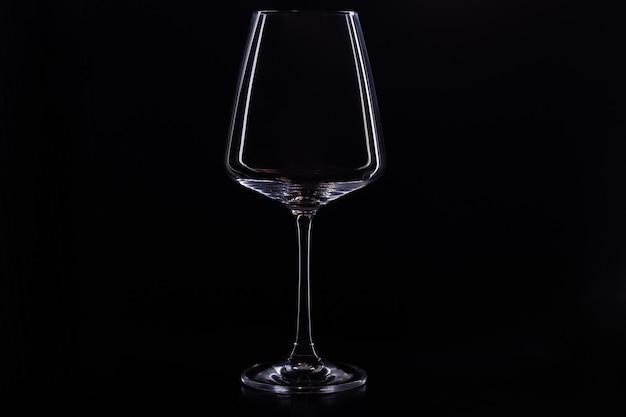 Пустой стакан для вина на черном фоне. силуэт бокал красного вина на черном фоне