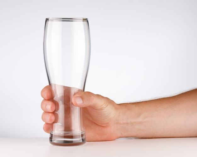 Empty glass in his hand on a white background