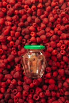 Пустая стеклянная банка для приготовления малины на текстуре красной спелой малины на заднем плане