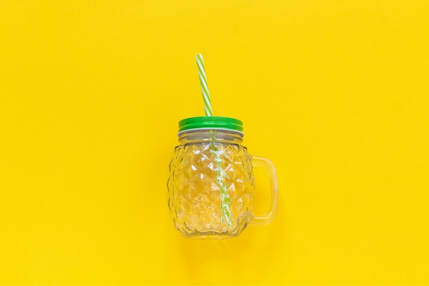 Empty glass jar in form of pineapple with green lid and straw for fruit or vegetable beverages