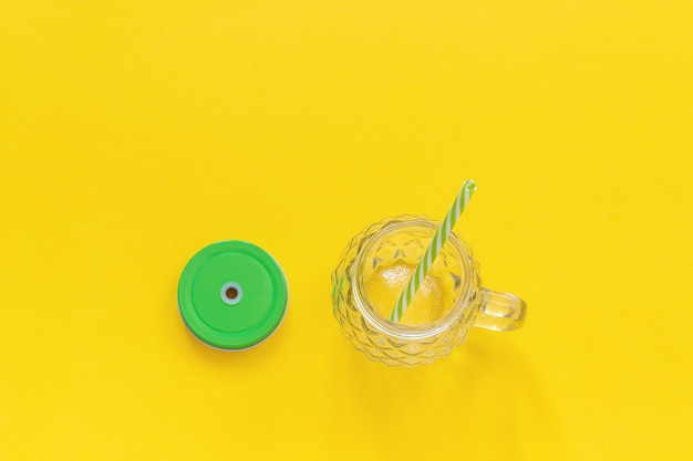 Empty glass jar in form of pineapple with green lid and straw for fruit or vegetable smoothies, cocktails and other beverages