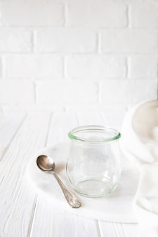 白い背景の上の素朴な木製のテーブルの上の空のガラス瓶