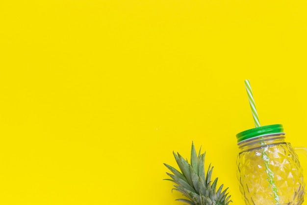 Empty glass jar with green leaves pineapple and straw for fruit or vegetable smoothies