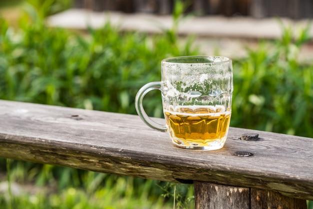 自然のベンチで軽いビールの空のグラス