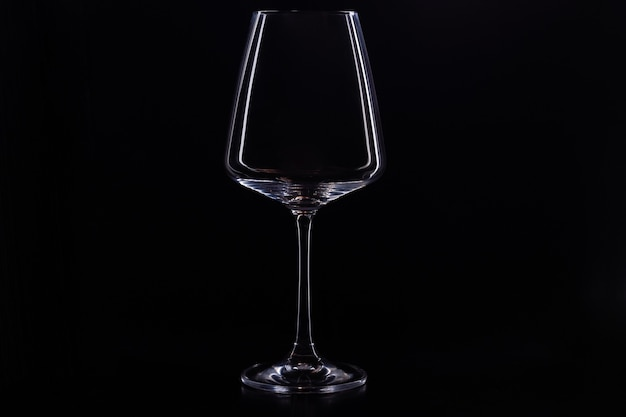 Empty glass for wine on a black background. red wine glass silhouette on black background