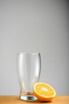 Vetro vuoto con mezza arancia sullo scrittorio di legno