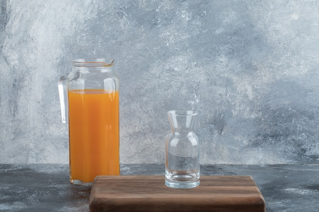 Empty glass on wooden board with jug of juice.