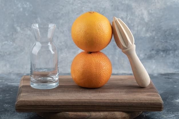 Bicchiere vuoto, alesatore in legno e arance su tavola di legno.