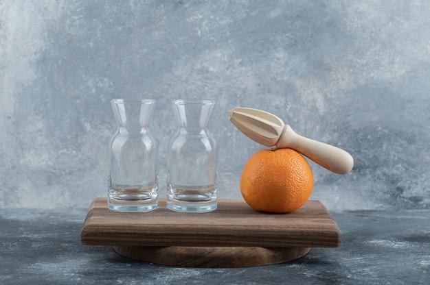 空のグラスと木の板にオレンジ。
