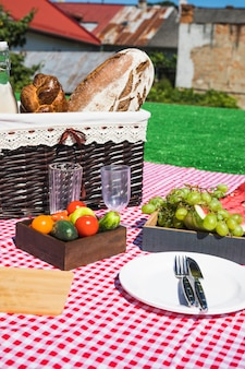 Empty glasses; cutlery; fruits and vegetables with picnic basket on blanket