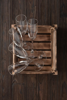 Пустые бокалы для шампанского в деревянном ящике к новогоднему столу