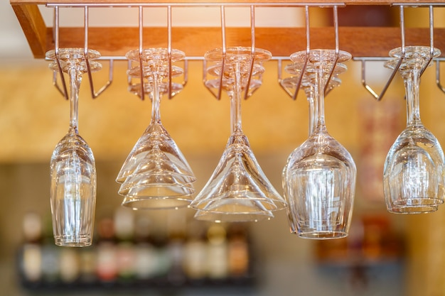 Empty glasses for wine above a bar rack