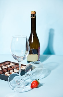 Empty glasses with box of chocolates and bottle
