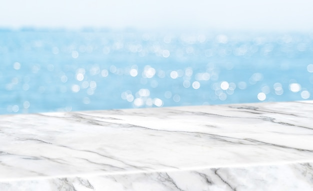 Empty glossy white marble table top with blur sky and sea boekh background