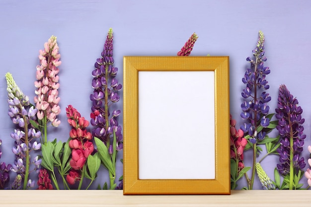 Empty gold frame for photo on backdrop of flowers.