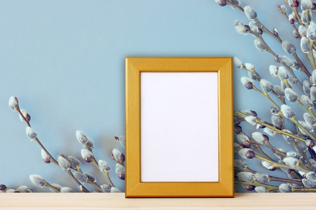 Empty gold frame for photo of willow branches