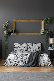 Empty gold mockup frame placed on a wall shelf with books and green plants in dark bedroom interior