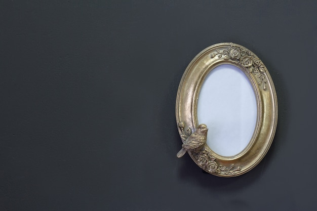 Empty gold vintage oval frame in victorian style on a gray wall, background or concept