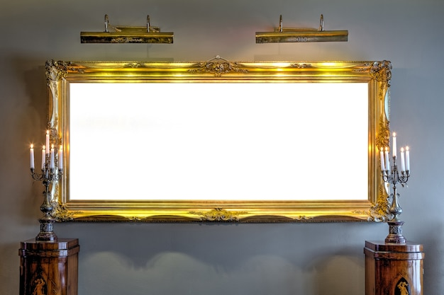 Empty golden painting frame on the wall in archaic manor house museum.